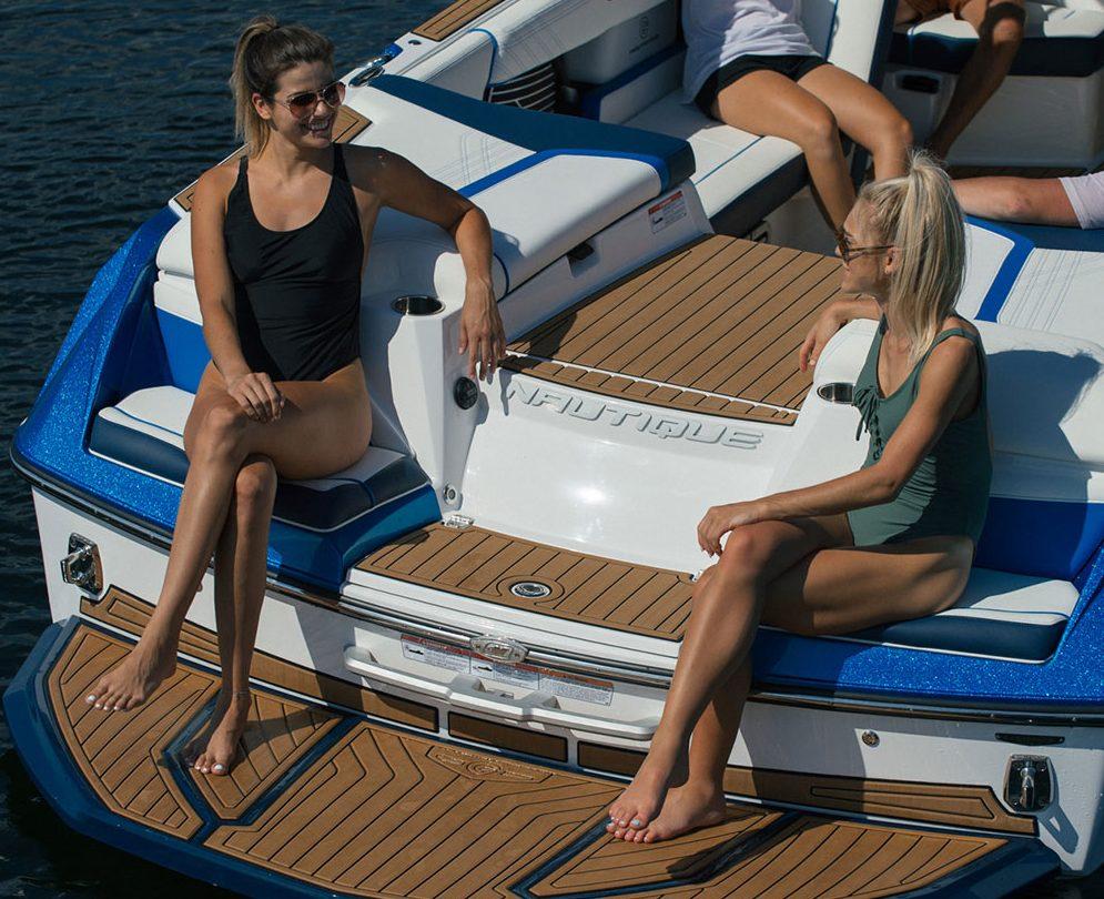 girls sitting on stern of nautique boat